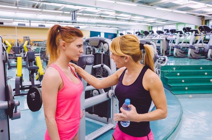 Entrenador personal animando a la mujer triste después del entrenamiento