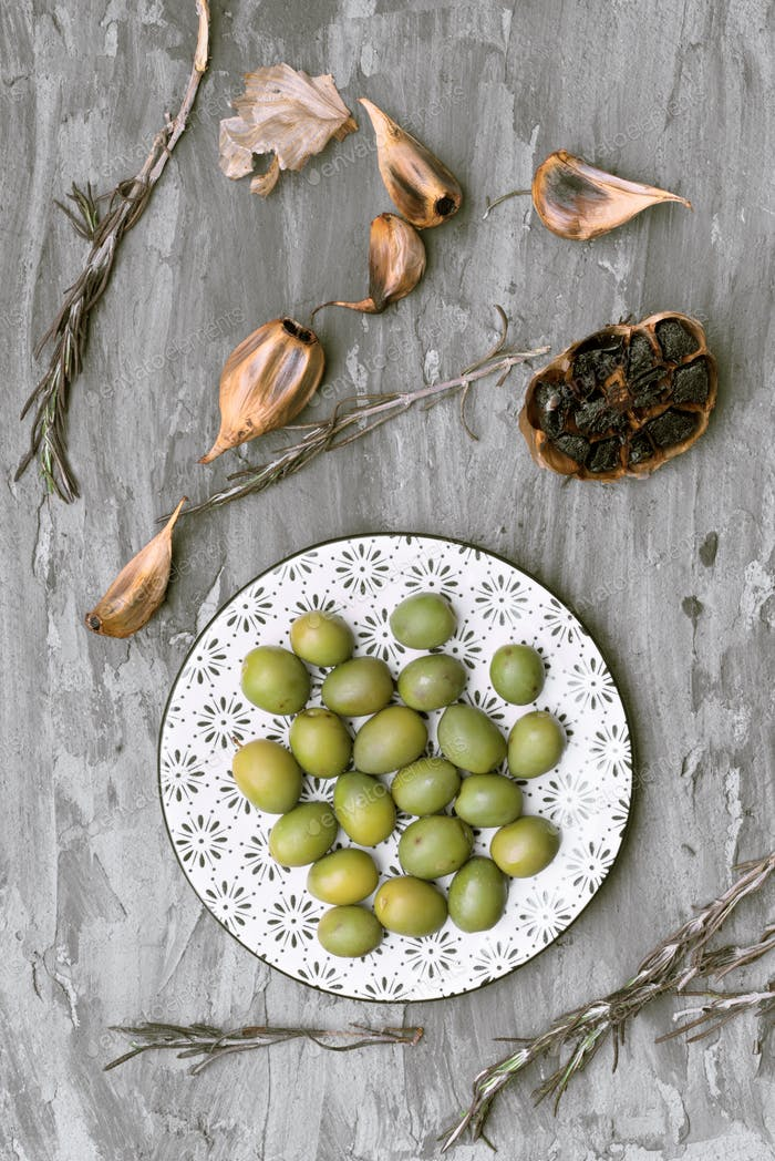decorated porcelain plates with green and black olives, in gray rustic setting