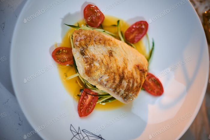 Fillet of grilled and baked codfish served with vegetables and oil sauce, on a dish in a restaurant