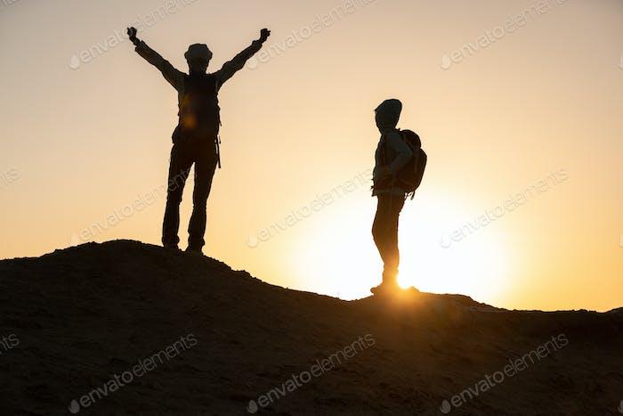 Two women backpackers hiking on  desert