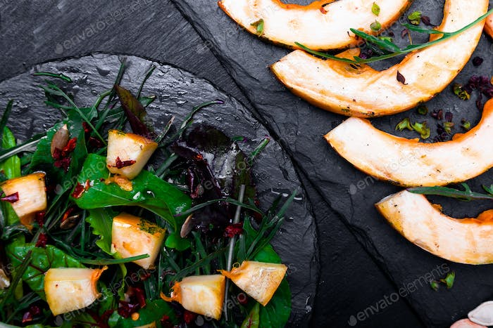 Warm pumpkin salad with mixed leaf on black slate plate on black background. Grilled pumpkin.