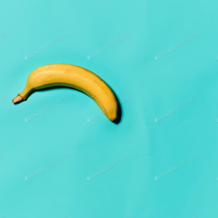 Single banana against blue background