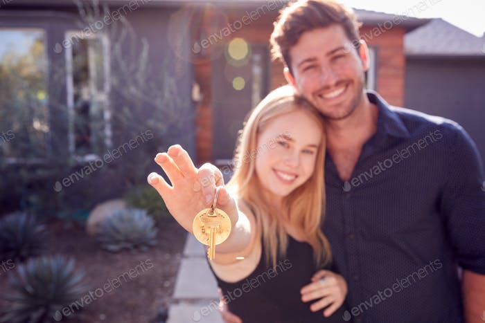Portrait Of Couple With Pregnant Wife Standing Outdoors In Front Of New Home Holding Keys