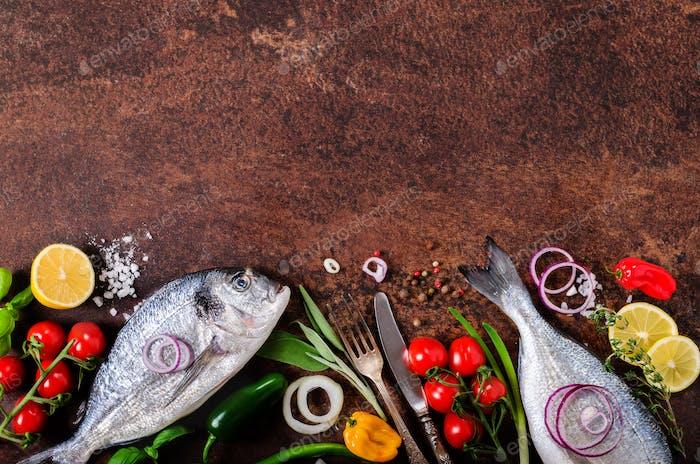 Dorada, fresh fish with vegetable, lemon, herbs, onion, paprika, cherry tomatoes, onion, salt
