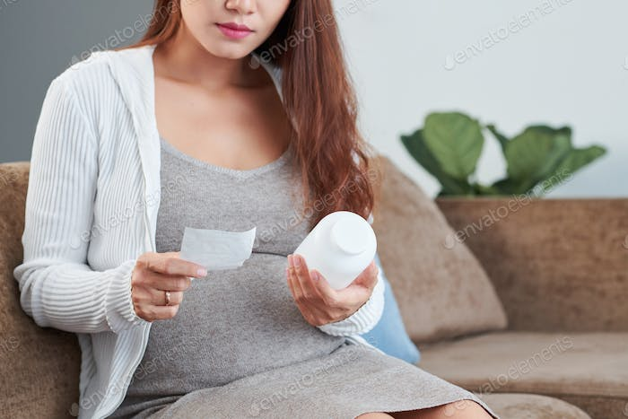 Pregnant woman reading doctors prescription