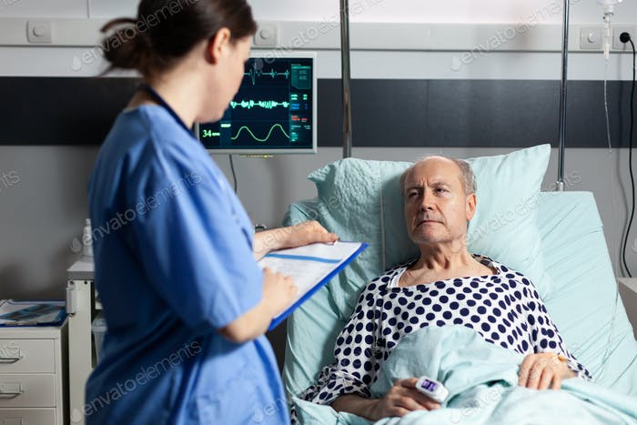 Medical assistant checking treatment of senior man