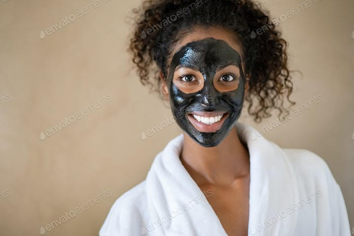 Smiling woman with charcoal face mud