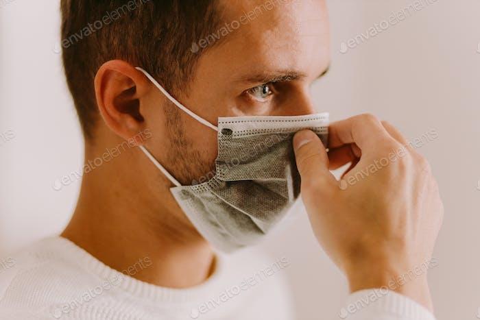 Mann mit Gesichtsmaske für Virenpräventionsmaßnahmen auf Quarantäne zu Hause