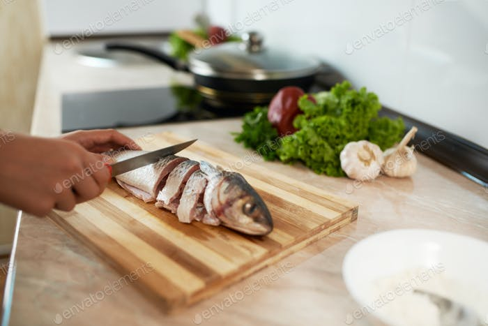 girl cut slice of  fish
