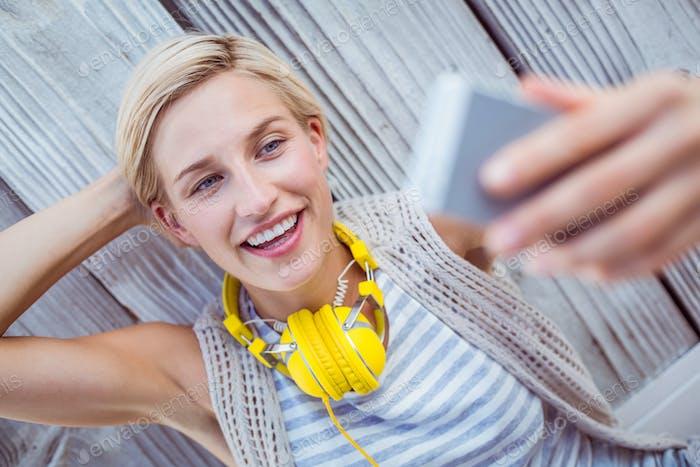 Pretty blonde woman taking selfie on wooden background