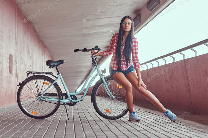 Stylish brunette girl posing with city bike against a pink wall.