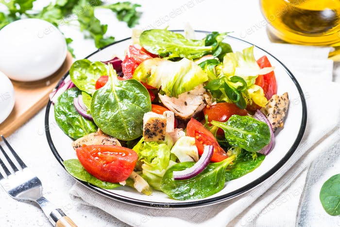 Green salad with chicken and vegetables on white