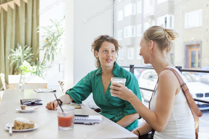 Mid adult women talking at cafe table