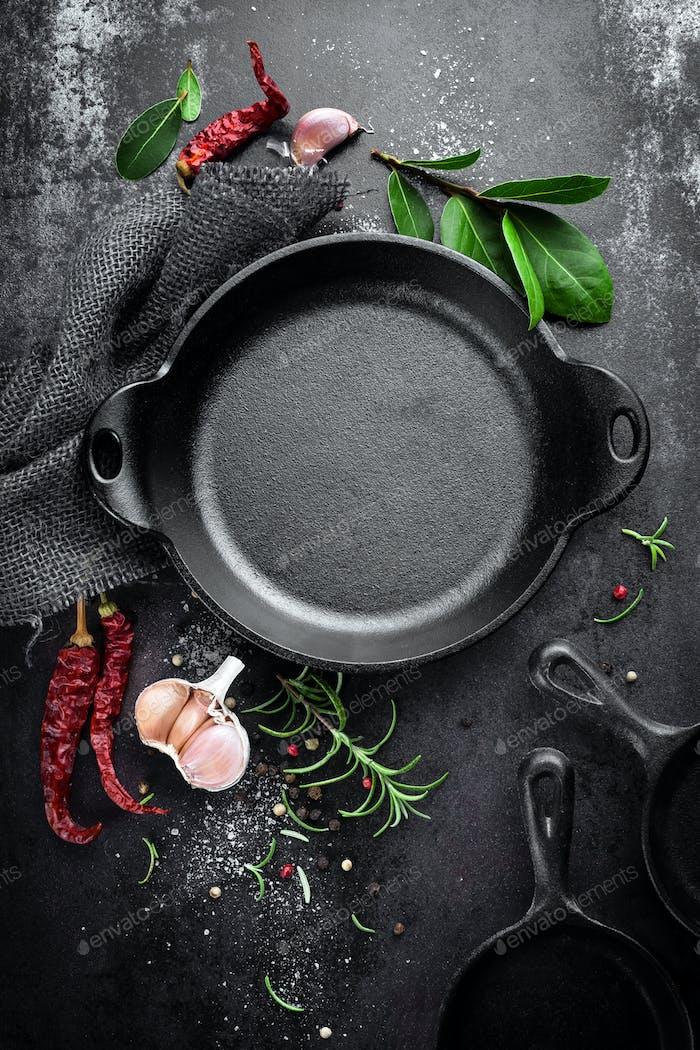 sartén de hierro fundido y especias sobre Fondo culinario de Metal negro, vista desde arriba