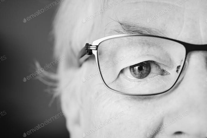 Portrait of white elderly woman closeup on eyes wearing specatac