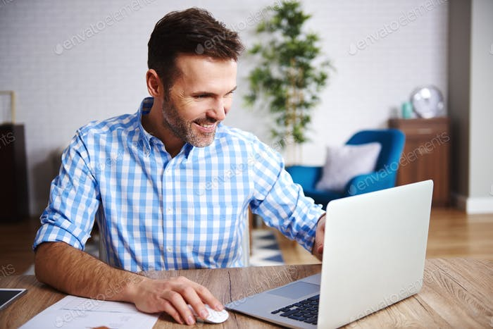 Happy man using laptop in his home office
