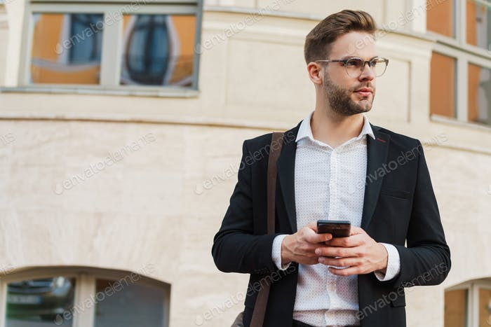 Handsome unshaven businessman using mobile phone on city street