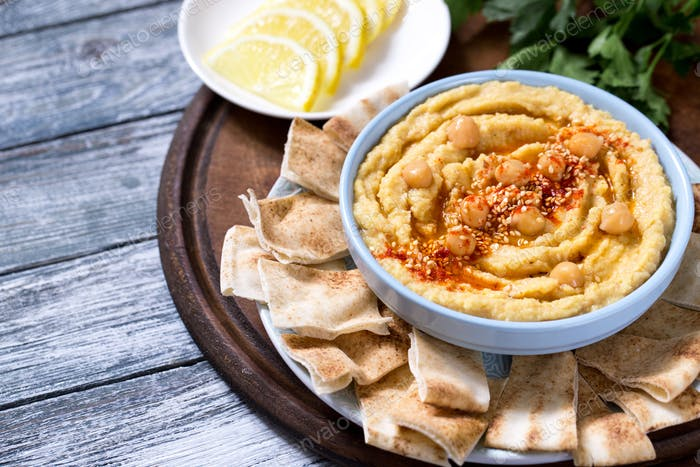 A bowl of creamy homemade hummus with olive oil and pita chips