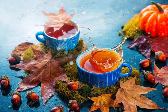 Splash of hot tea in a blue ceramic cup. Autumn drink photography with fallen maple leaves on a dark