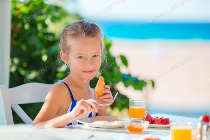 Lunch time. Little girl having breakfast at outdoor cafe with sea view