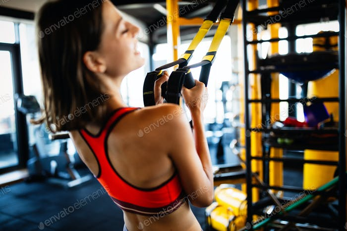 Beautiful fit young woman training in gym