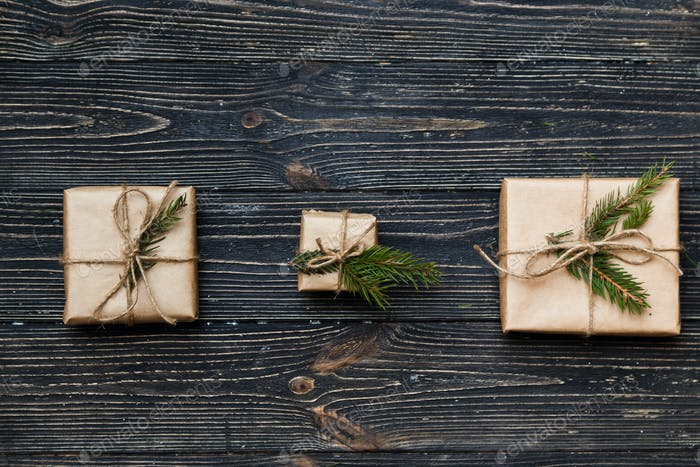 Three Vintage gift boxes with spruce branches on wooden background