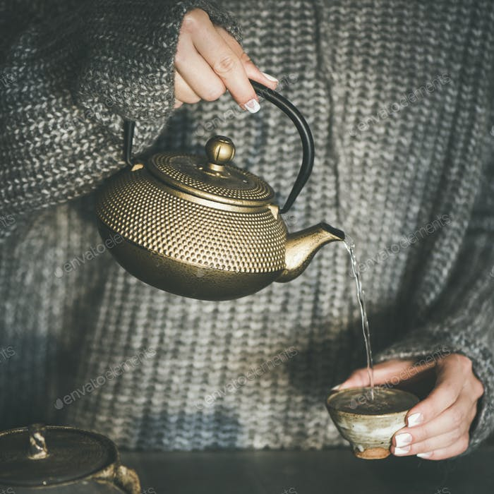 Female pouring green tea from pot into cup, square crop
