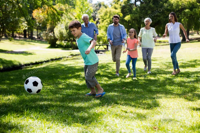 Multi generation family playing football in park