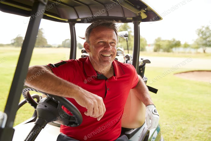 Mature Man Playing Golf Driving Buggy Along Course To Green On Red Letter Day