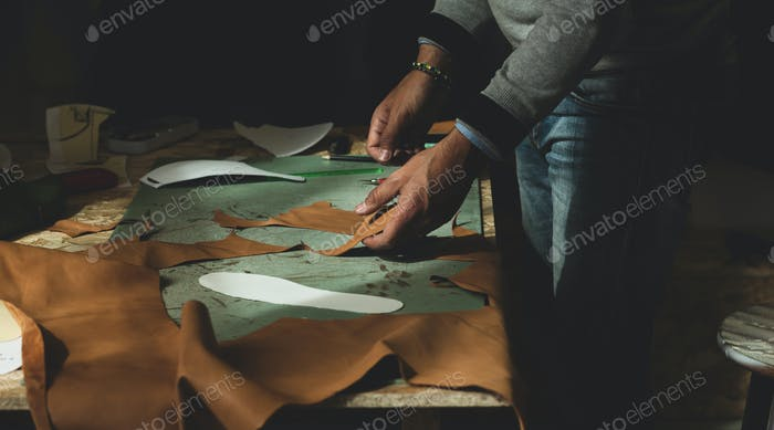 Shoemaker cutting leather