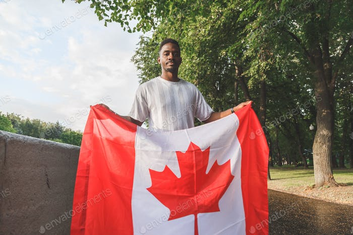 Handsome Afro American man with Canadian flag seriously looking at camera, standing outdoors.