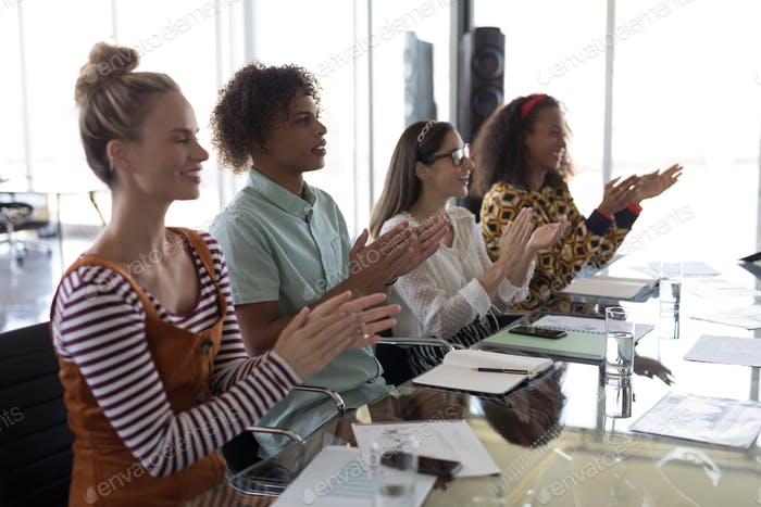 Side view of young multi-ethnic business colleagues smiling and clapping hands in modern office