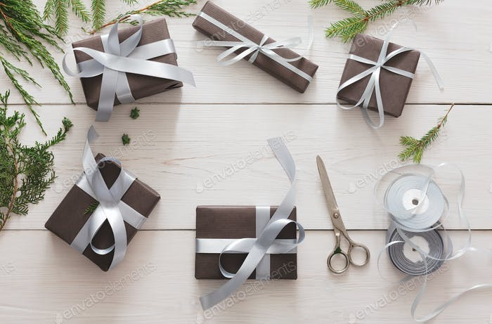 Gift wrapping. Packing modern christmas present in boxes