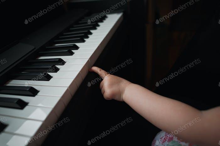 Die Hand eines kleinen Mädchens neben dem Klavier. Ein kleiner Finger versucht die Tasten zu drücken. Kein Gesicht. Nah dran.