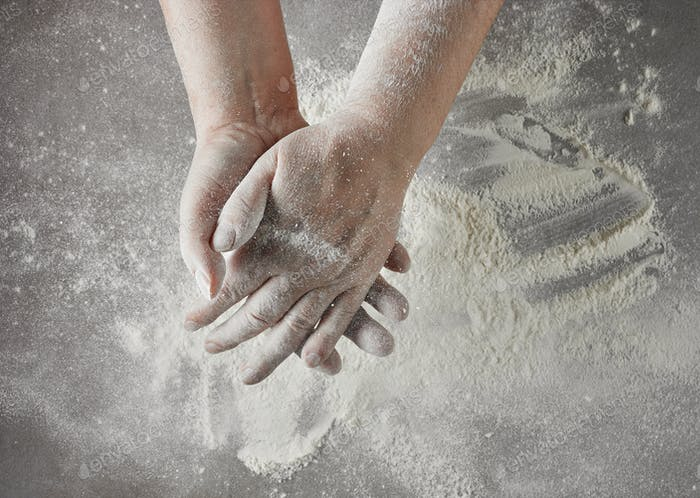 Bäckerhände mit Mehl in Bewegung