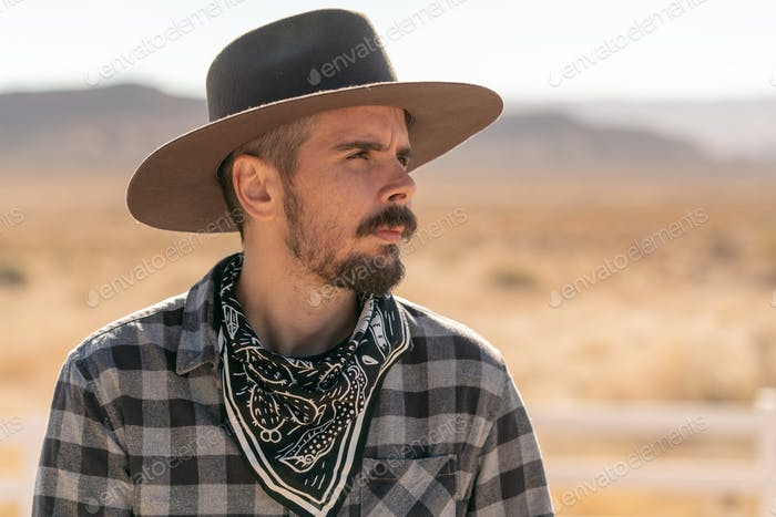 Cowboy with grey hat, moustache and checked shirt in the desert