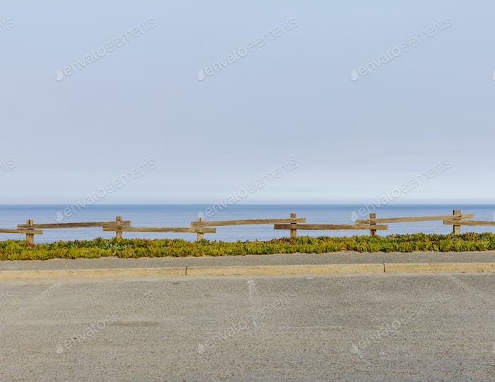 Parking lot with fencing and ice plant ground cover, by the ocean