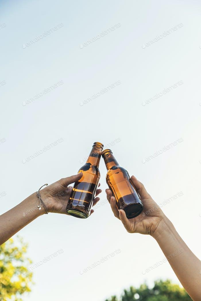 Female friends cheers clinking bottles of beer.