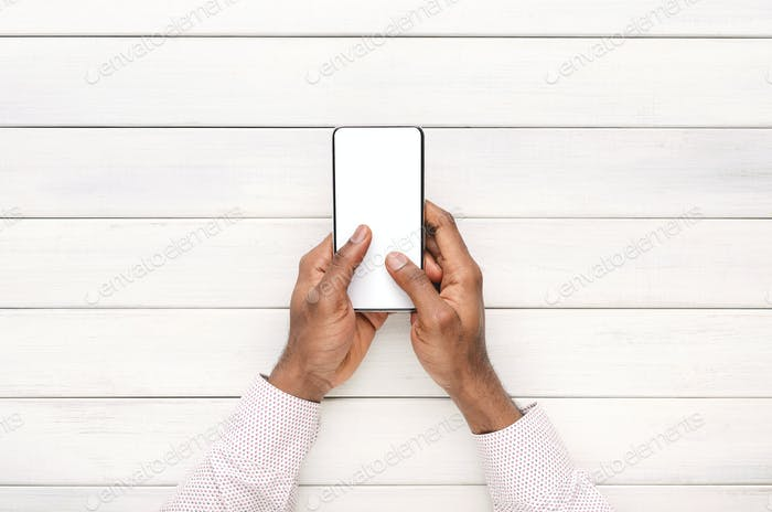 Hands using smartphone with blank screen over white wooden background
