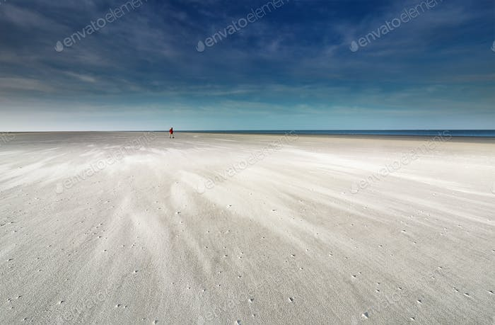 lone man walking on sand beach by North sea