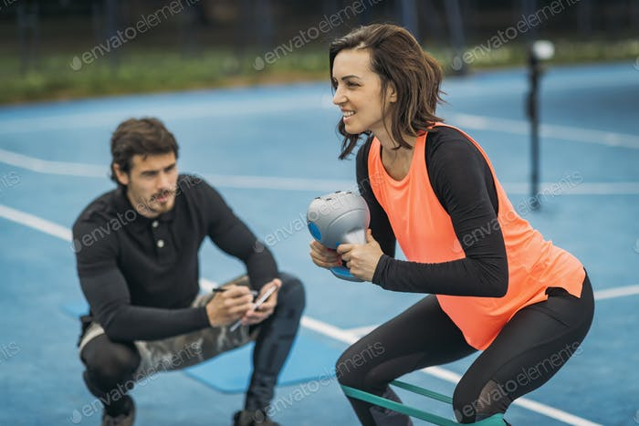 Personal Trainer with Female Client, Kettlebell Exercise, Outdoors