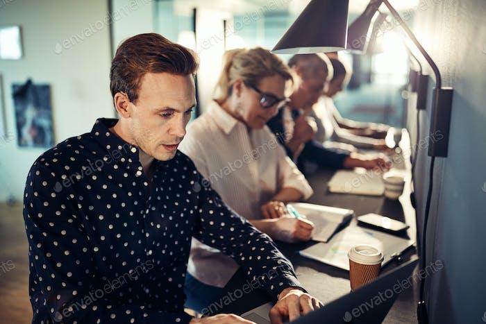 Designer arbeiten mit einem Laptop mit Kollegen im Hintergrund