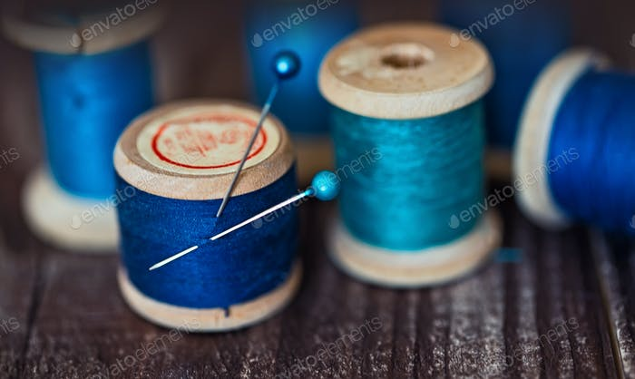 Collection of aqua spools threads arranged on a grunge wooden table