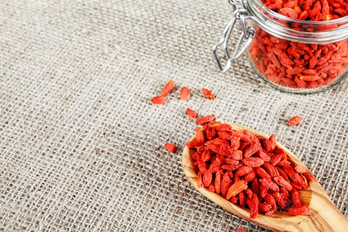 Dried goji berries on a wooden spoon.