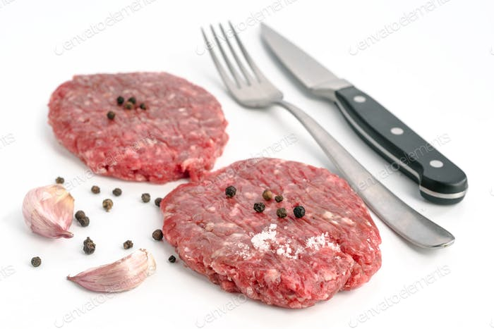 uncooked hamburgers and other ingredients isolated on white