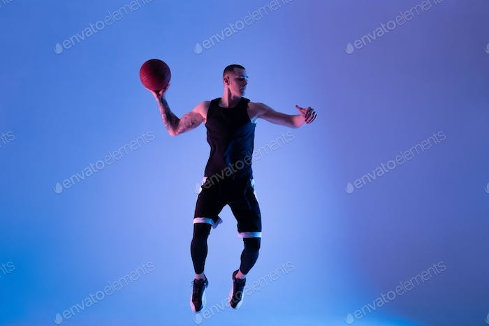 Basketball player jumping and trowing ball under blue light