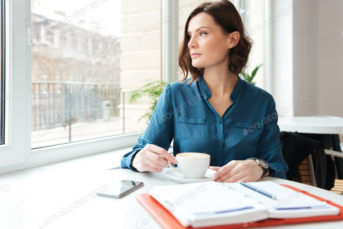 Attractive woman sitting at the cafe table and drinking coffee
