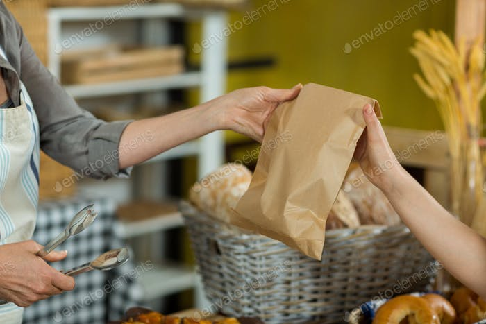 Mid section of saleswoman giving a parcel to costumer at counter