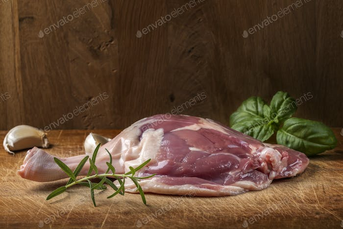 One duck raw leg and herbs on wood