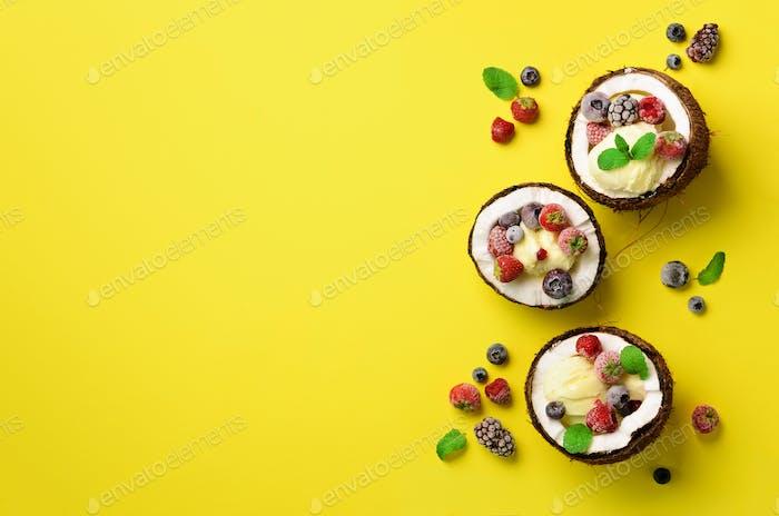 Kokos-Eis mit frischen Beeren in Kokosnusshälften auf gelbem Hintergrund mit Kopierraum. Oben